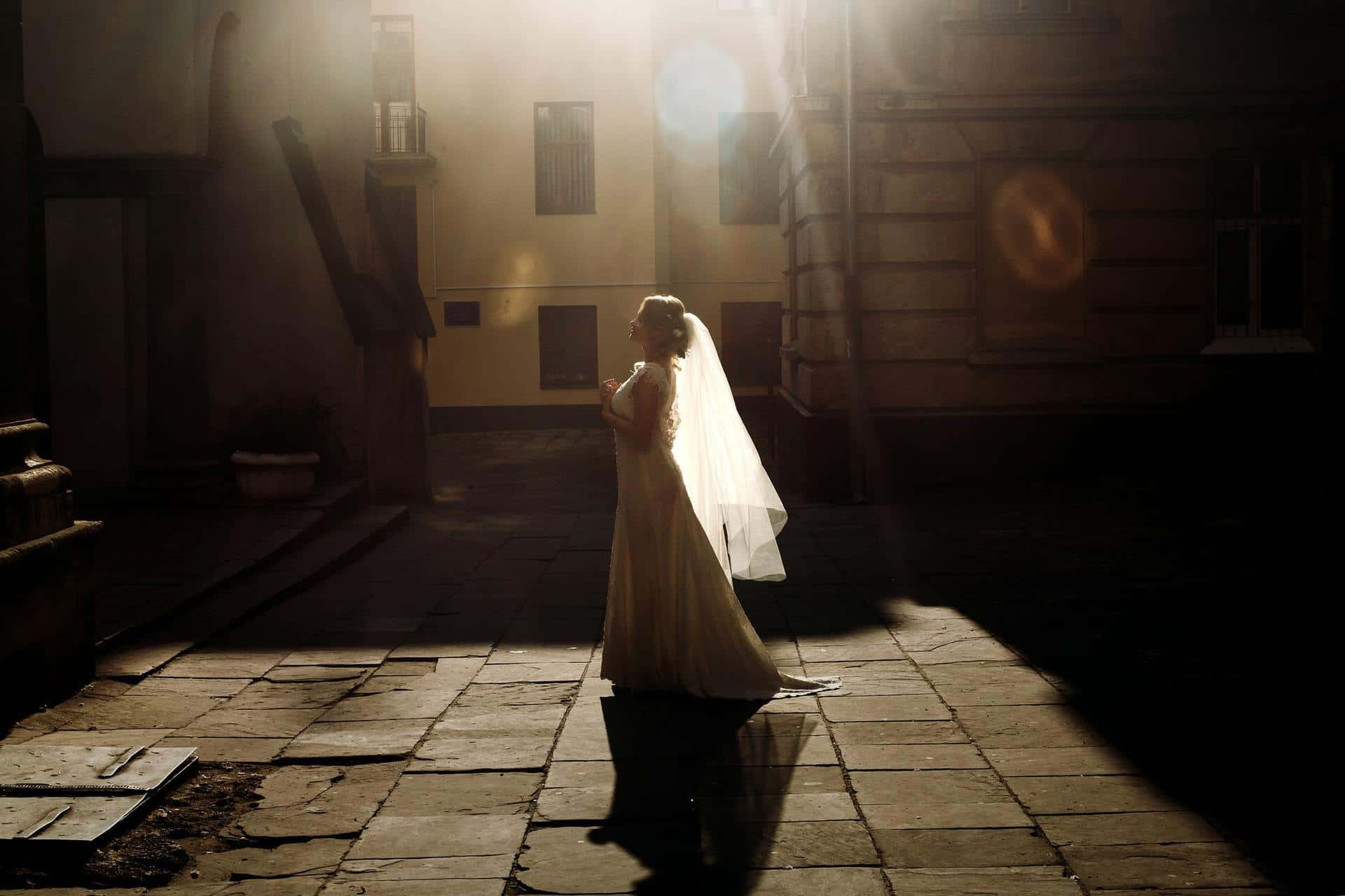 Beautiful fairytale bride in vintage white wedding dress walking down