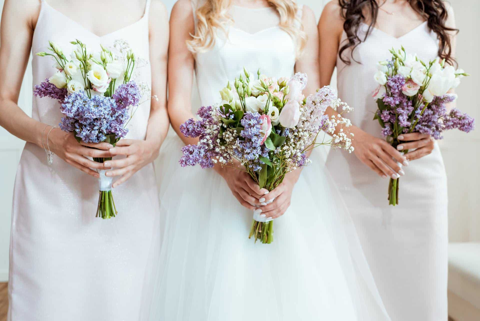 cropped shot of bride with bridesmaids holding bouquets